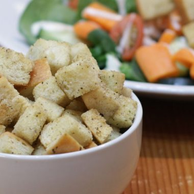 homemade croutons in a white bowl with salad behind it