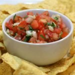 pico de gallo in a white bowl surrounded by tortilla chips