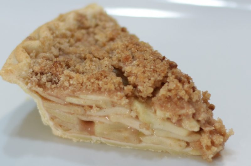 Slice of apple crumb pie on a white plate