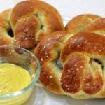Three homemade soft pretzels on a plate next to a bowl of mustard.