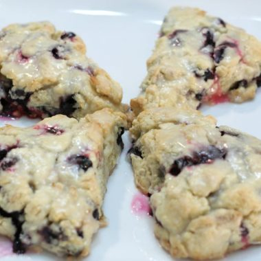 Four blueberry scones on a white plate
