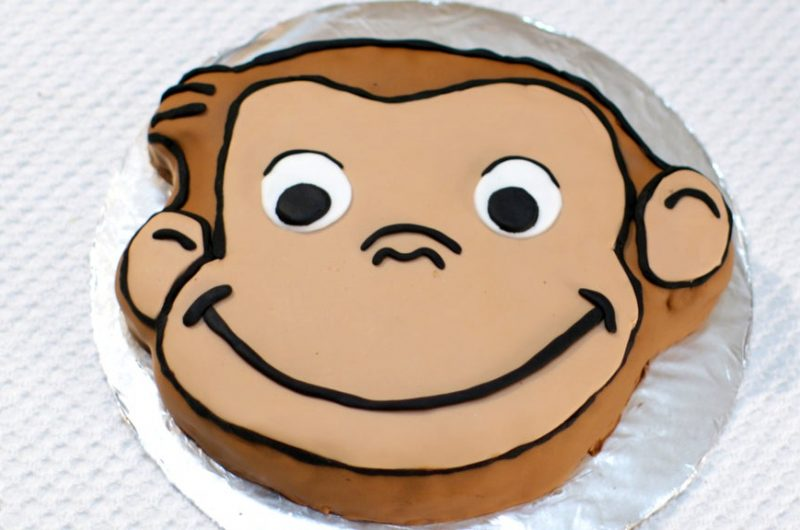 Curious George cake on a cake board covered in aluminum foil.