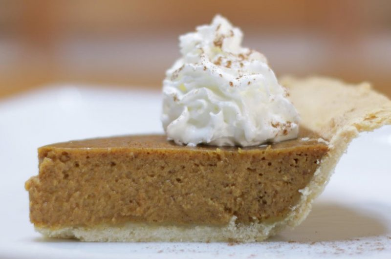 Slice of homemade pumpkin pie on a white plate.