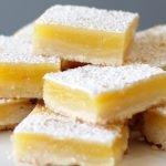 Homemade lemon bars stacked on a white plate