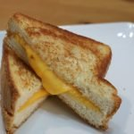 Perfect grilled cheese sandwich stacked on each other on a white plate.