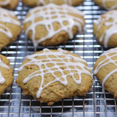 Several glazed pumpkin cookies on a wire cookie rack.