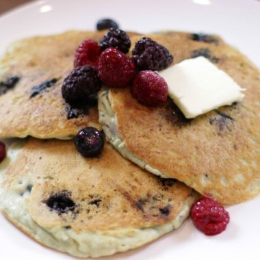 Keto blueberry pancakes with butter and berries on a white plate