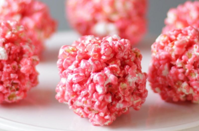 several pink popcorn balls on a white plate.