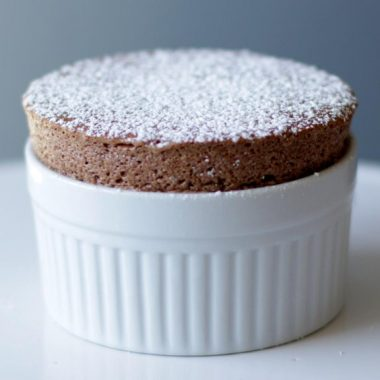 Easy chocolate souffle on a white cake pedestal in a white ramekin
