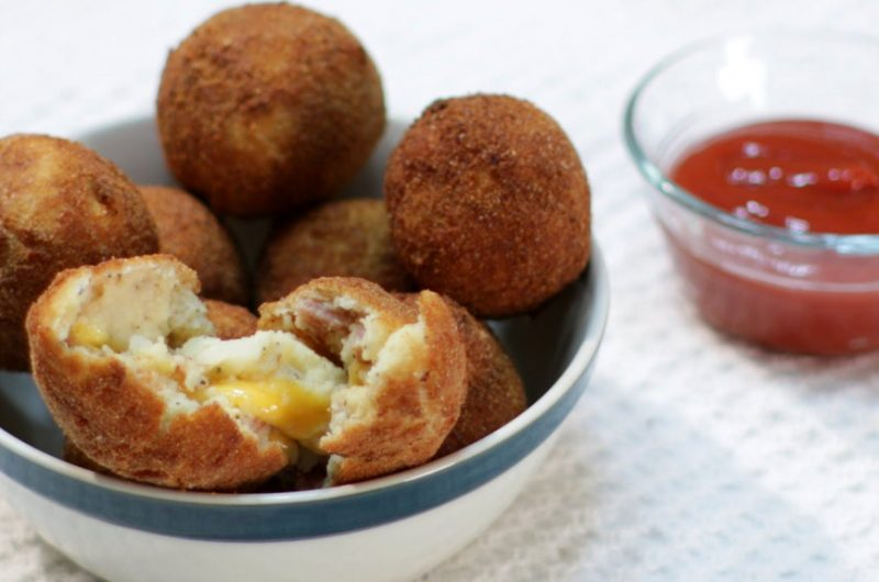 Several bacon and cheese mashed potato balls in a bowl on a table.