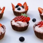 Strawberry cheesecake mousse chocolate cups on a white cutting board