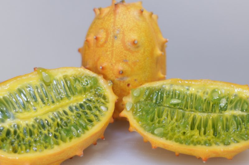 two halves of a kiwano melon on a cutting board