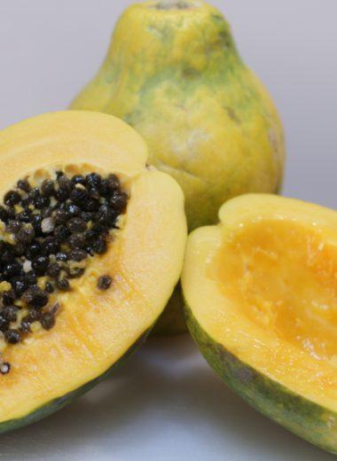 Cut open papaya on a white cutting board