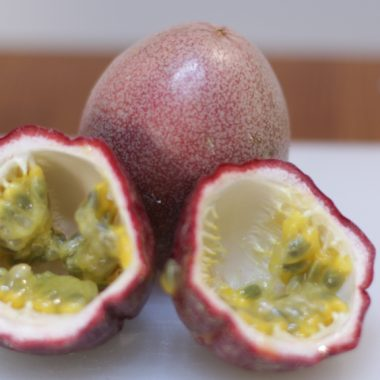 Passion fruit cut open on white cutting board.