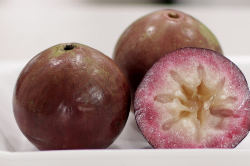 Three star apples on a white plate.
