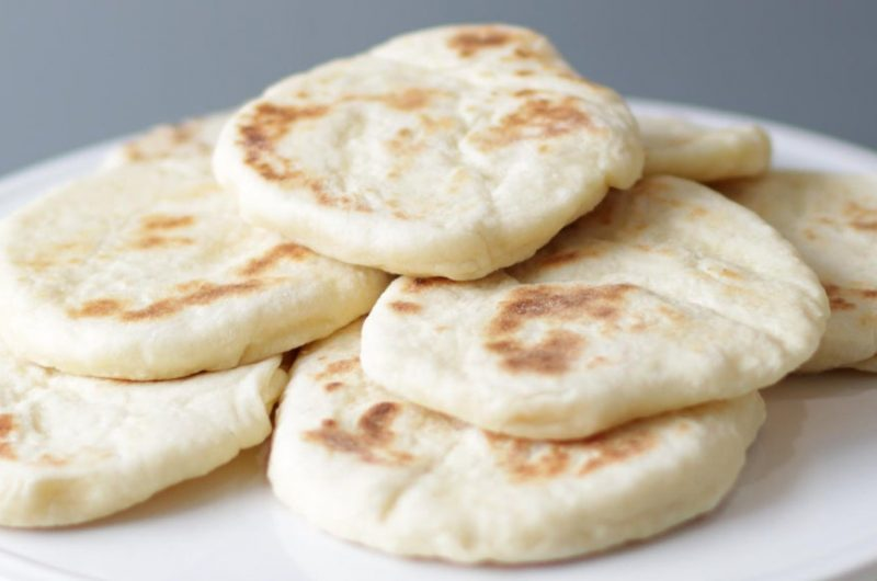 easy flatbread piled up on a white plate