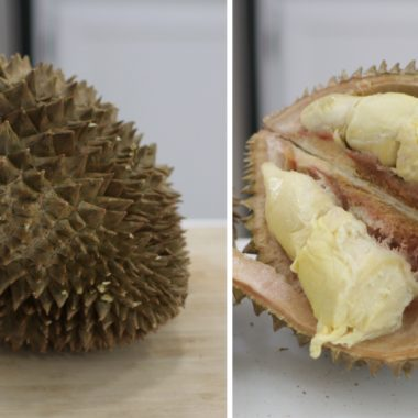 Sliced Durian Fruit next to a whole one on a counter.