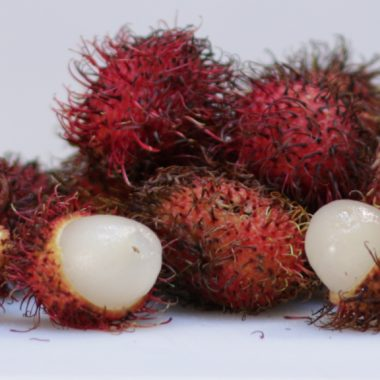 how to eat rambutan pile of rambutans on a white cutting board