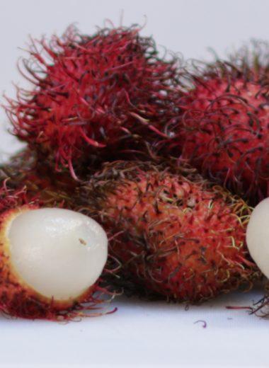 how to eat rambutan pile of rambutans on a white cutting board