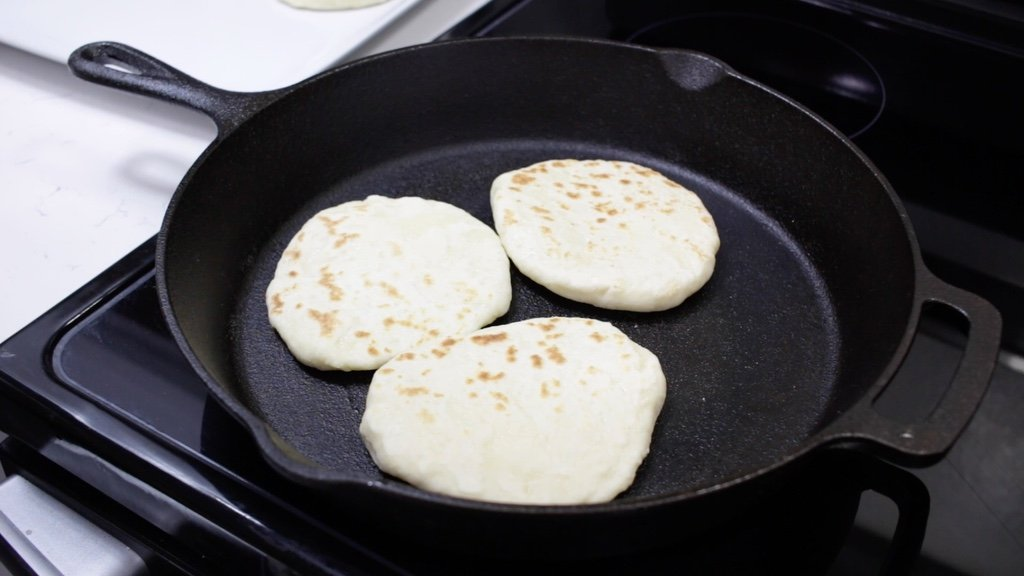 Cast iron skillet with three small flatbread in it.