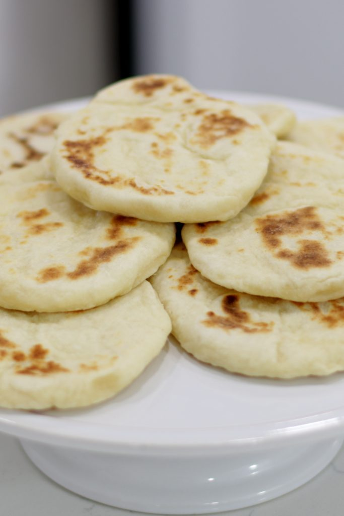 Pile of flatbread on a white plate.