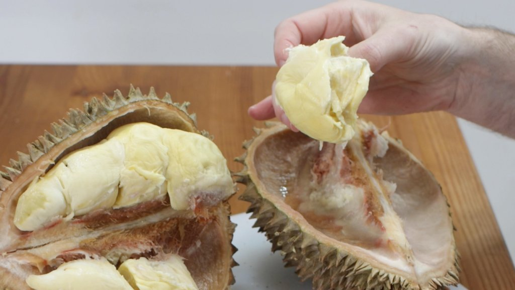 Hand holding the durian flesh