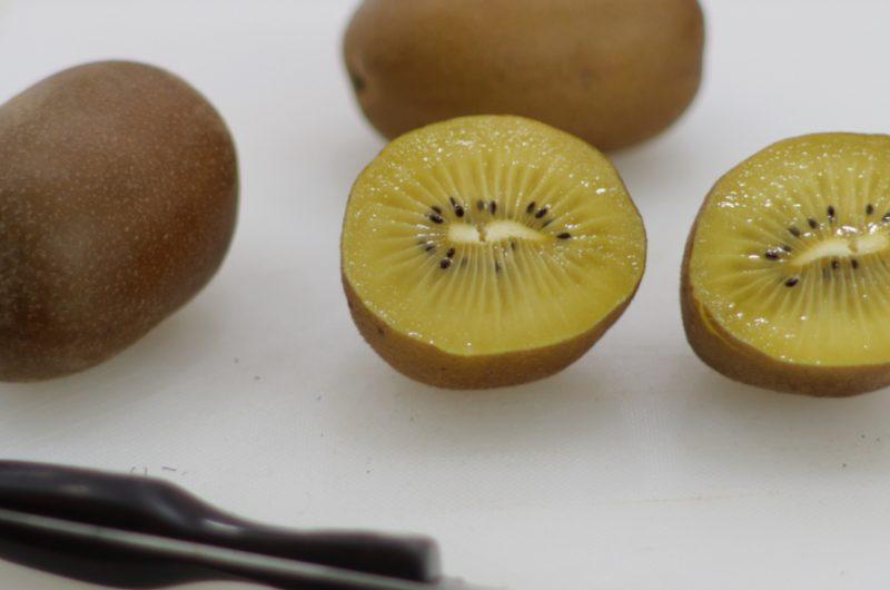 Kiwi gold cut in half on a white cutting board