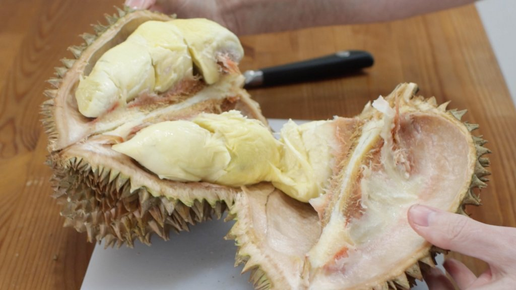 Durian fruit pulled apart on a white cutting board.