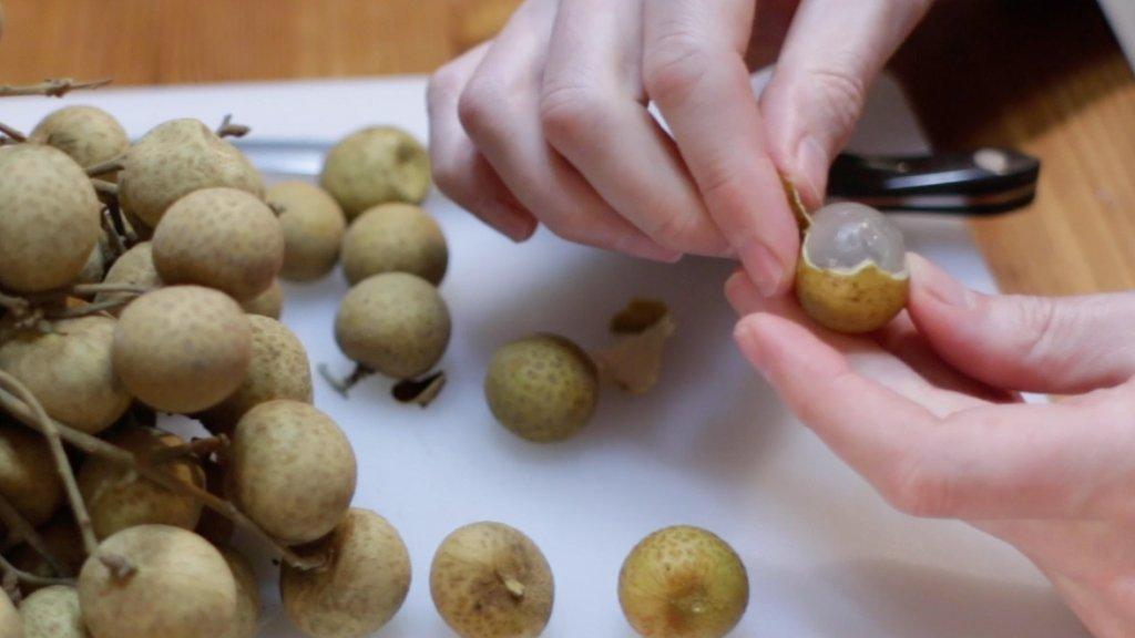 Hand peeling the longan fruit.