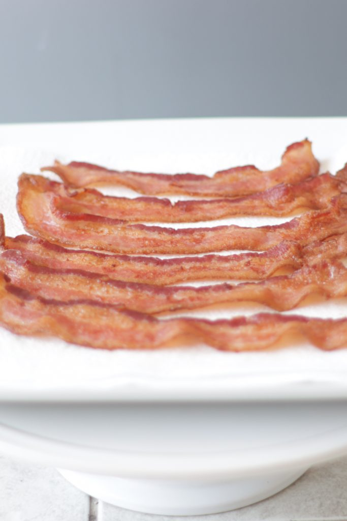 Plate with paper towel and 6 strips of air fryer bacon.