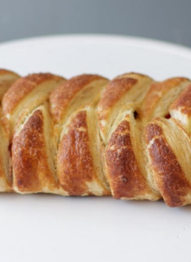 Braided strawberry puff pastry on a white plate