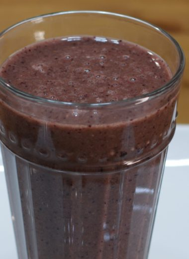Healthy smoothie in a glass on a white plate.