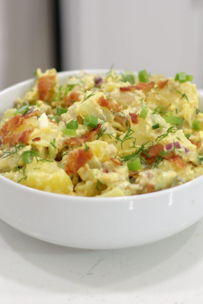 Large white bowl full of potato salad