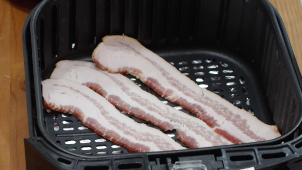 3 slices of thick-cut bacon in an air fryer basket.