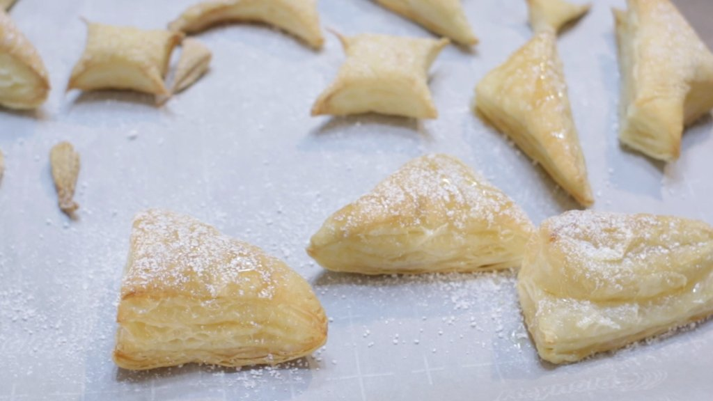 Baked puff pastry scrapes on a sheet pan lined with parchment paper.