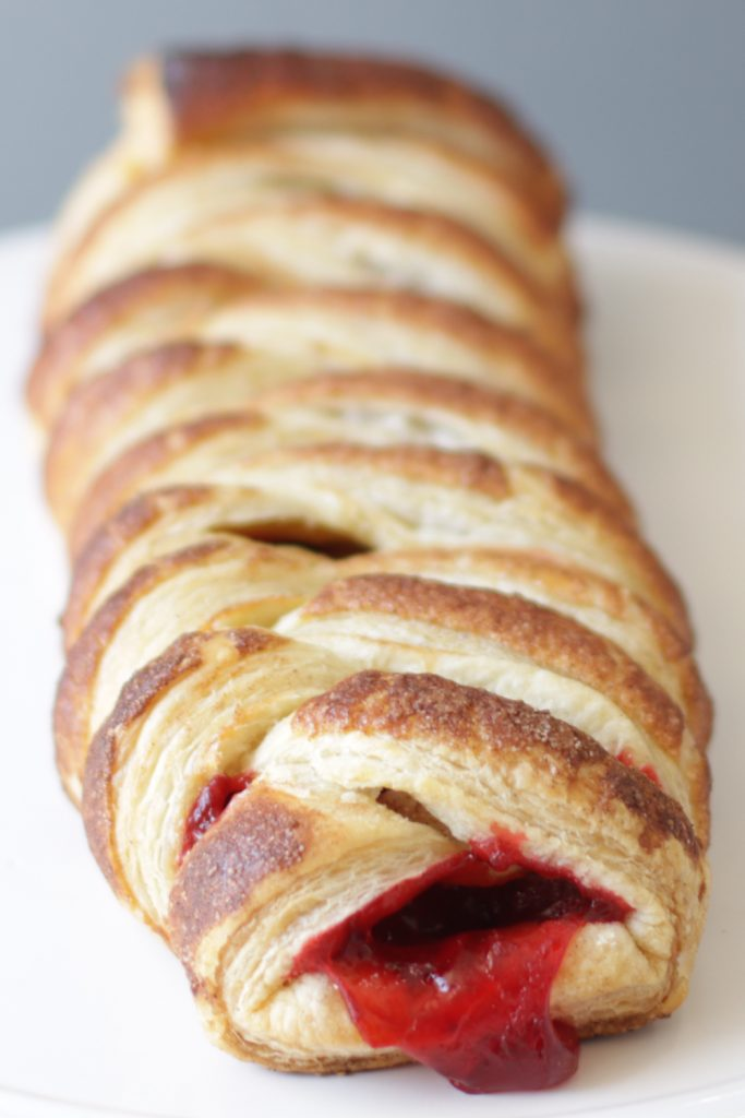 Braided strawberry puff pastry on a white plate.