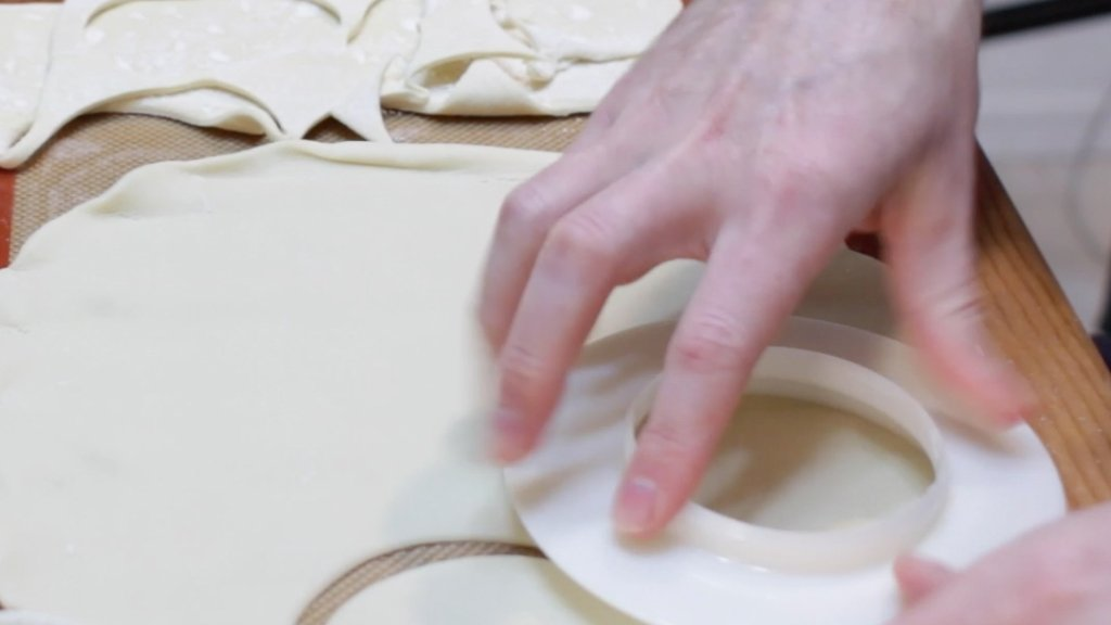 Hand cutting round circles out of a pie crust.