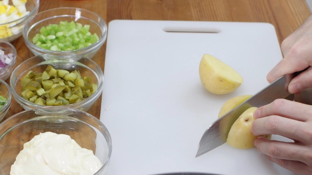 Hand with knife cutting Yukon Gold potatoes on a white cutting board.