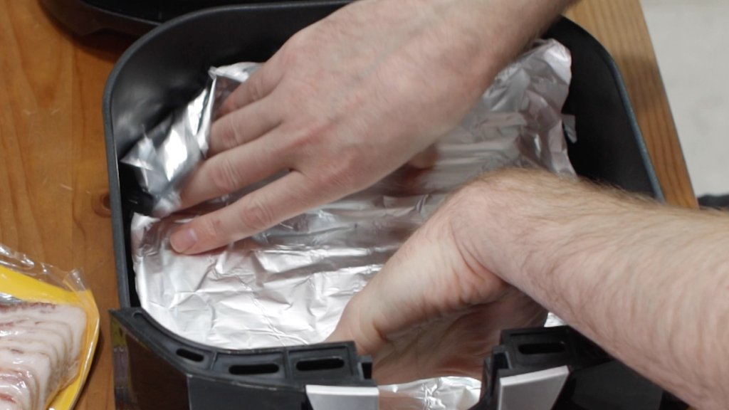 Hand placing foil in the bottom of an air fryer basket.