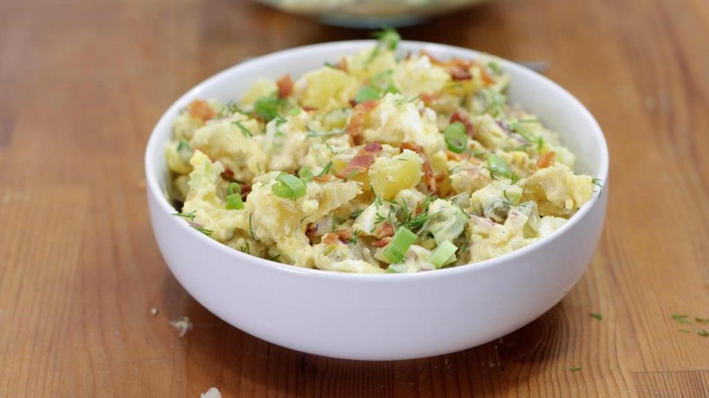White bowl full or garnished potato salad.