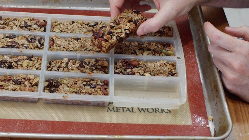 Handing holding freshly made homemade granola bar in hand.