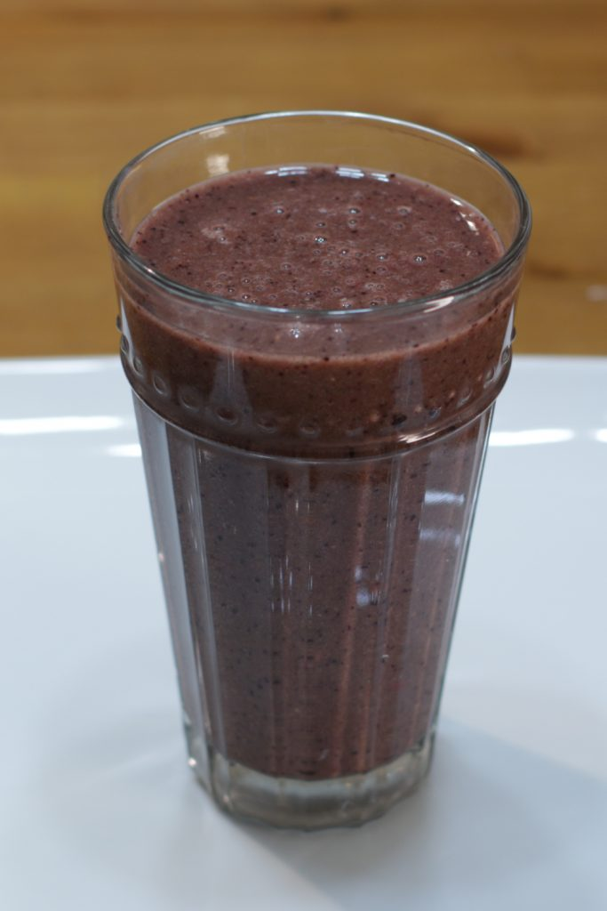 Large glass of healthy smoothie on a white plate.