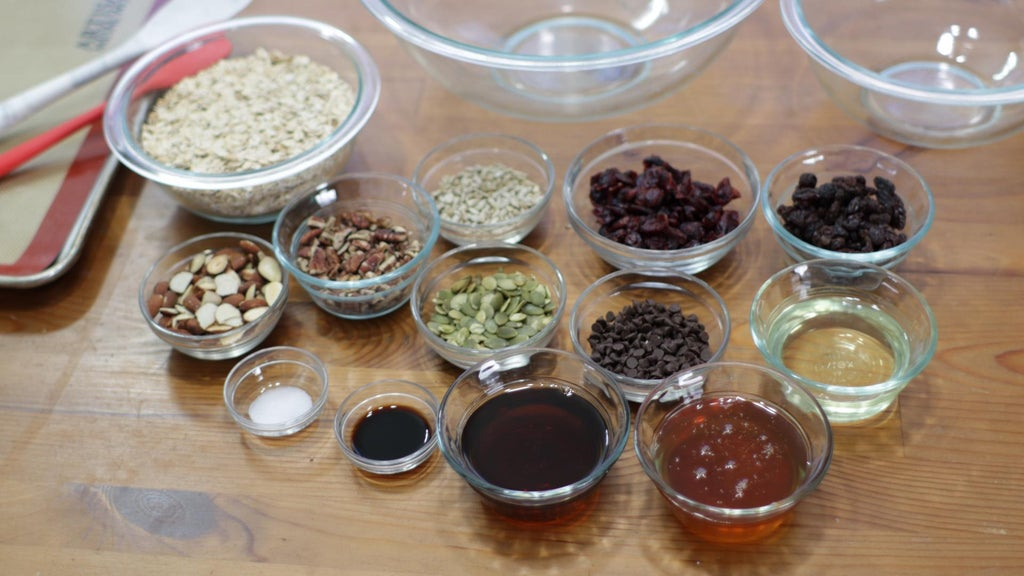 Several ingredients in glass bowls on a wooden table like oats, nuts, seeds, etc.