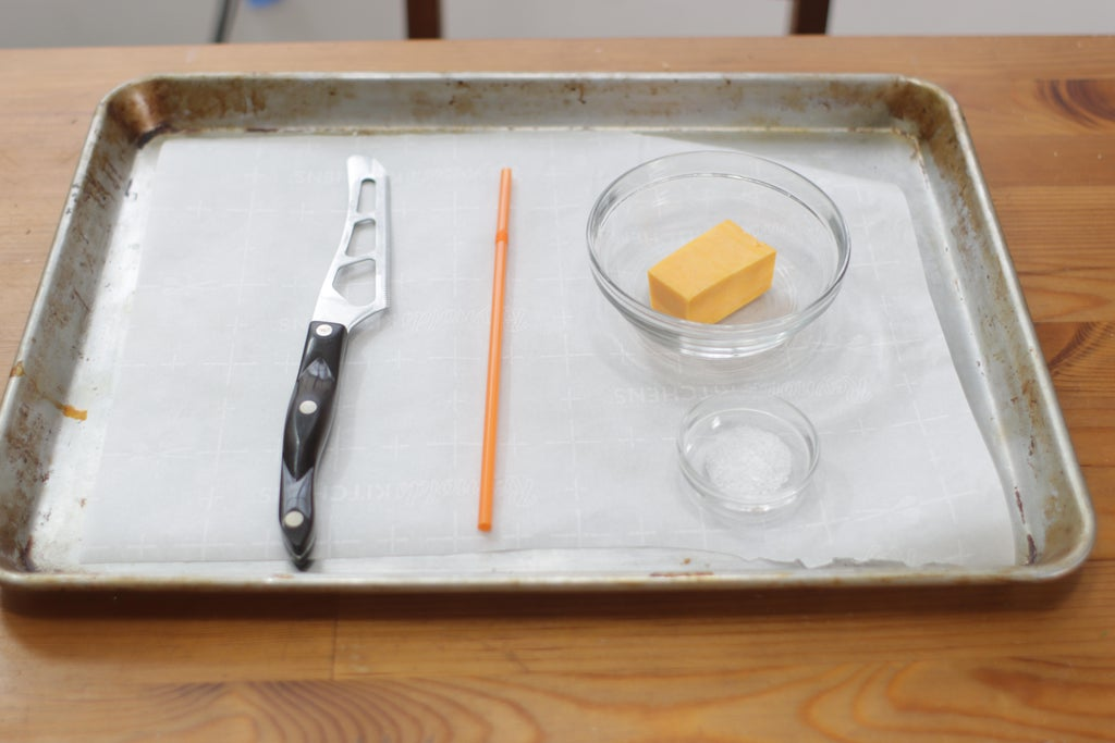 Cheddar cheese and salt in bowls on a sheet pan.