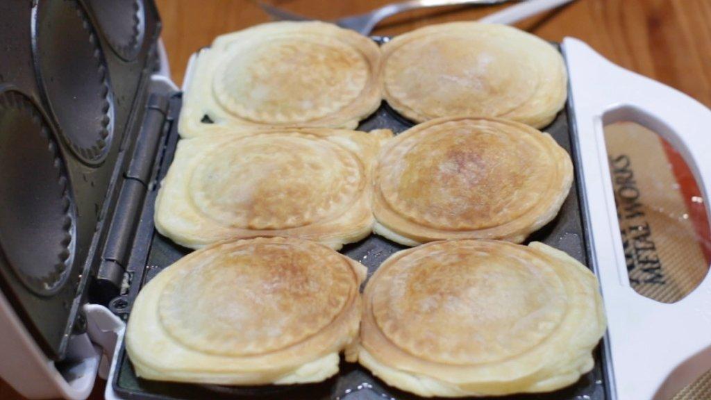 Freshly cooked mini pies in pie maker.