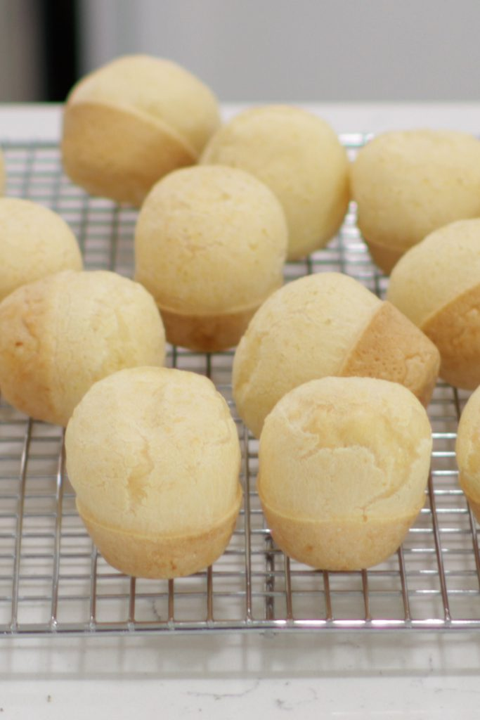 Several Brazilian cheese bread on a wire rack on a counter.