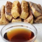 Stack of cinnamon french toast sticks on a plate.