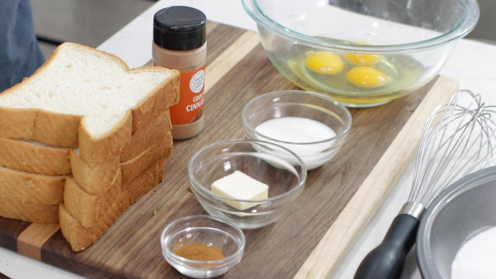 Several ingredients in glass bowls along with slices of thick bread on a wooden cutting board.