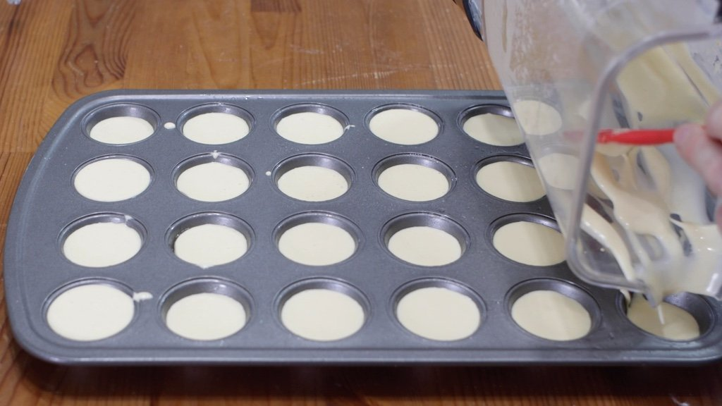 Blender pouring Brazilian cheese bread batter into a mini muffin pan.