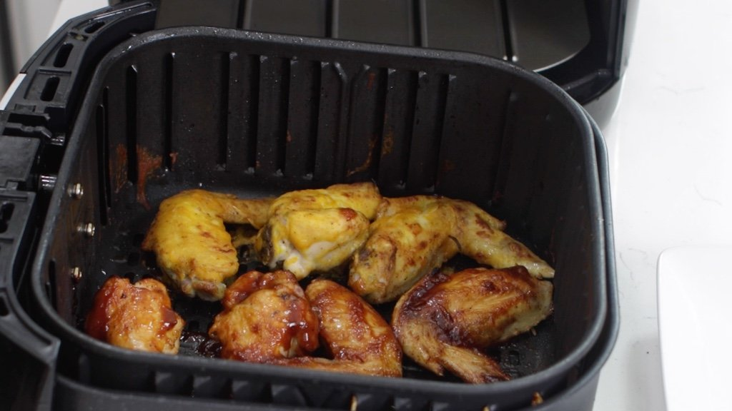 Fully cooked chicken wings in the air fryer basket.